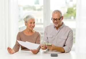 Seniorer med papirer, penger og kalkulator i hjemmet